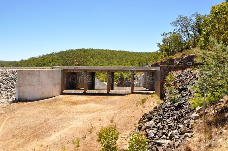 Spillway at the Serpentine Dam. Concrete spillway at the Serpentine Dam with lush native flora, sand and rock in Serpentine, Western Australia royalty free stock photography