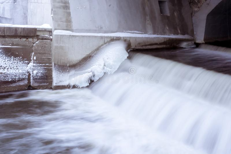 Spillway of a small dam with icy walls. Spillway of a small dam in winter with ice and snow on the concrete walls royalty free stock image