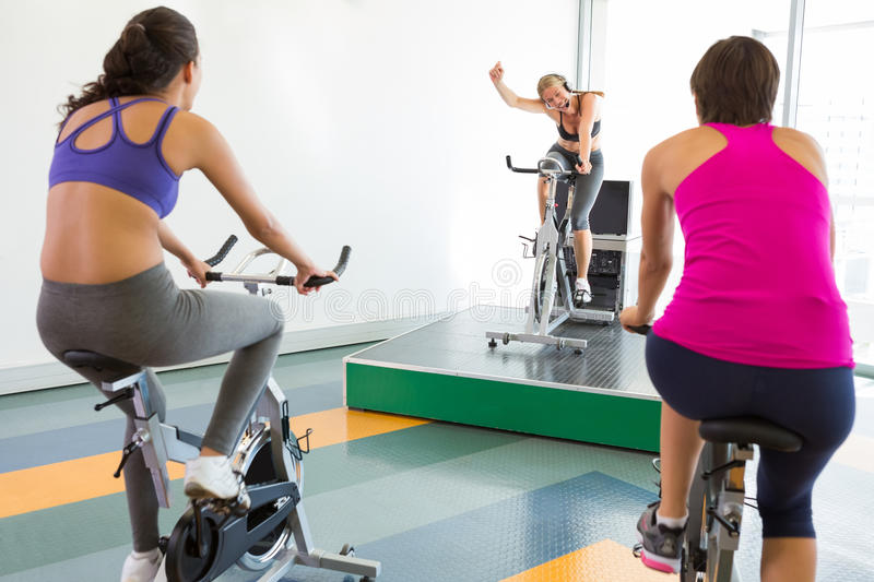 Spin class working out with motivational instructor. At the gym royalty free stock photo