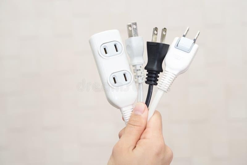 Spina di corrente della tenuta della mano e cavi di alimentazione elettrici fotografia stock libera da diritti