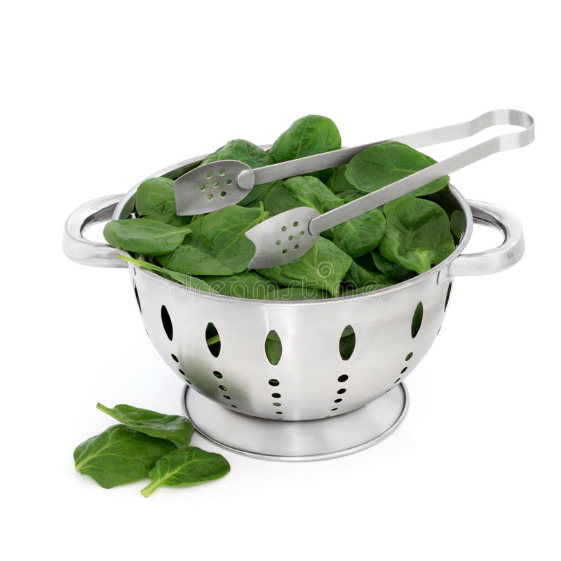 Spinach. Leaves in a stainless steel colander with metal tongs isolated over white background