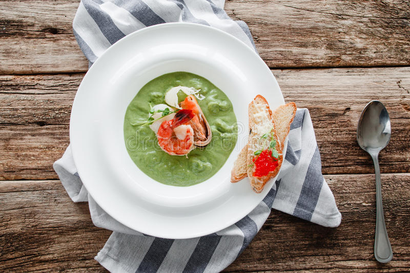 Spinach cream soup with shrimp and mussel flat lay stock image