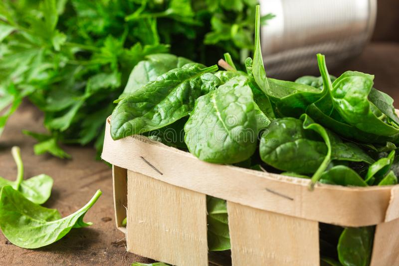 Spinach. Fresh organic spinach leaves in basket a wooden table. Diet, dieting concept. Vegan food, healthy eating. stock photos