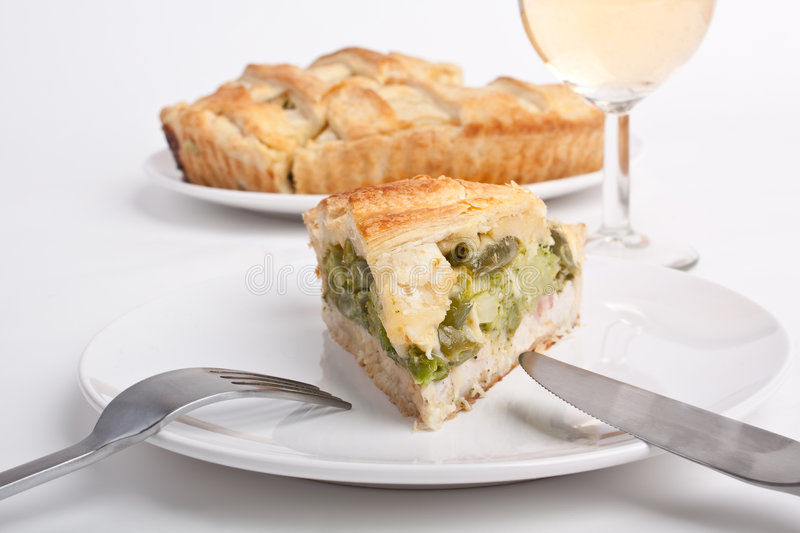 Spinach and green beans pie. Slice of spinach and green beans pie with a glass of wine and whole pie at the back stock photo