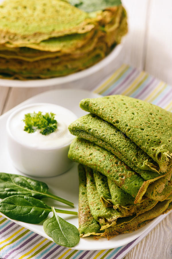 Spinach green pancakes crepes with sour cream. royalty free stock photography