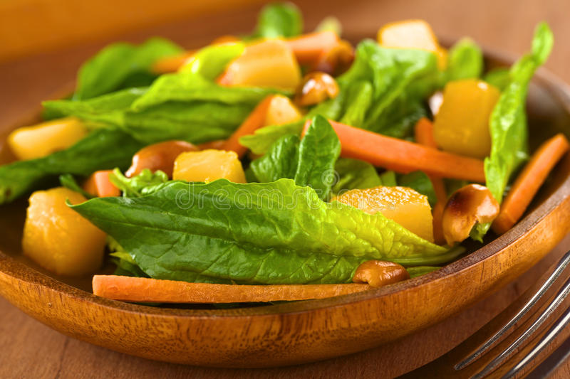 Spinach Mango Carrot Salad. Fresh spinach, mango and carrot salad with peanuts on wooden plate with fork (Selective Focus, Focus on the spinach leaf in the front stock image