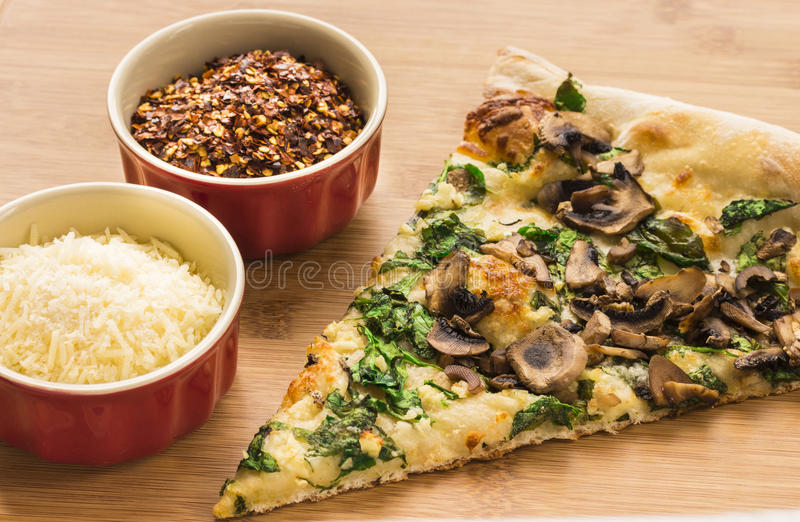 Spinach, Mushroom and Garlic Pizza. Slice of spinach, mushroom, garlic pizza on a bamboo board with grated parmesan and red pepper flakes stock photos