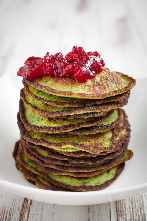 Spinach pancakes. Healthy and delicious spinach pancakes with lingonberry jelly royalty free stock image