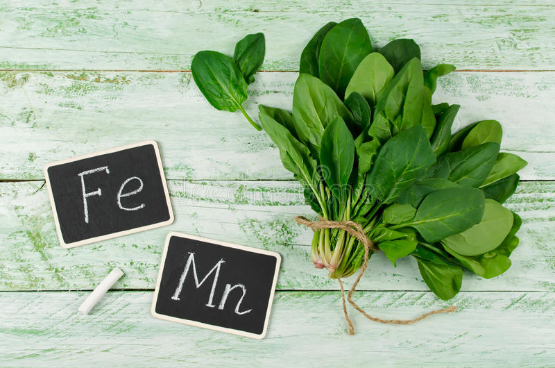Spinach rich in vitamin C, A, manganese and iron. Fresh bunch of spinach on a wooden background. Spinach is rich in vitamin C, A, manganese and iron stock photography