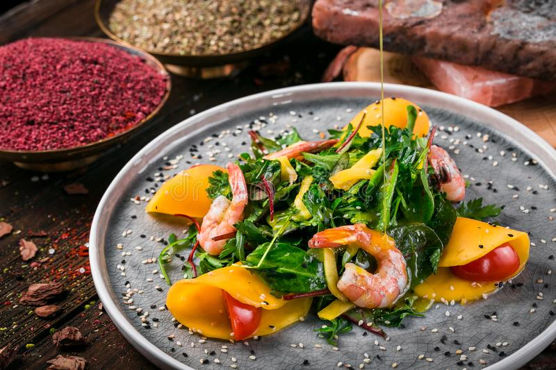 Spinach salad with rucola slices avocado tomato and shrimp royalty free stock image