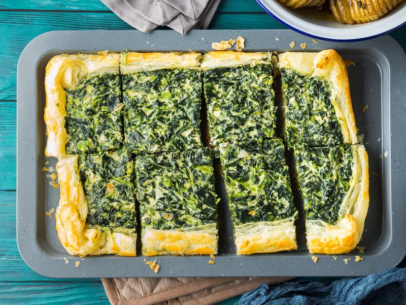 Spinach savory quiche with cream cheese. On baking tray royalty free stock images