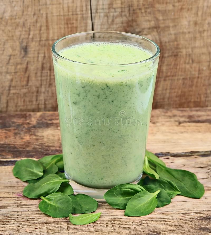 Spinach smoothie. With young leaves spinach on wooden tables stock photography