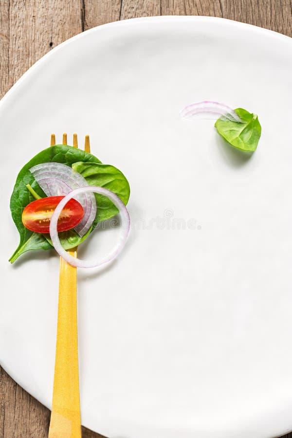 Spinats- und Kirschtomatensalat auf gelber Gabel lizenzfreie stockfotografie
