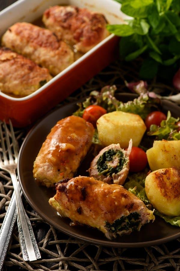 Spinazie en kaasvarkensvleesbroodjes met groenten worden gediend die stock foto