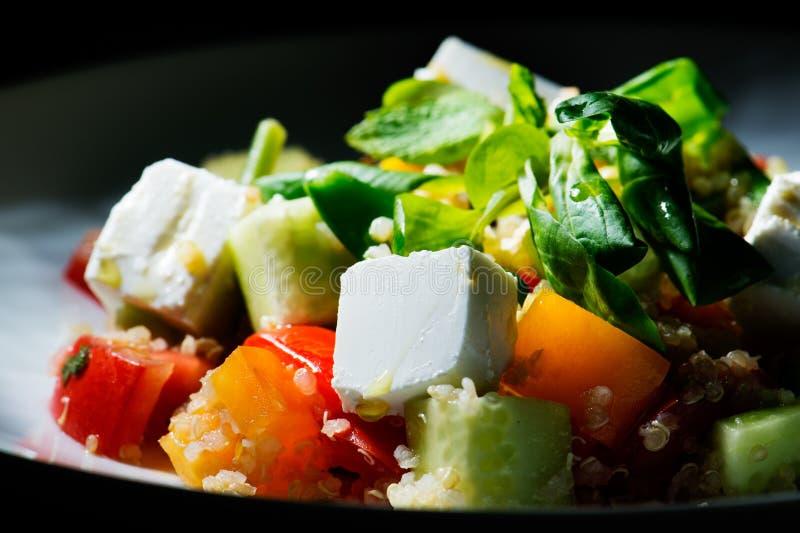 Spinaziesalade met quinoa en organische tomaten, gemarineerde tomaten en tomaten royalty-vrije stock afbeelding