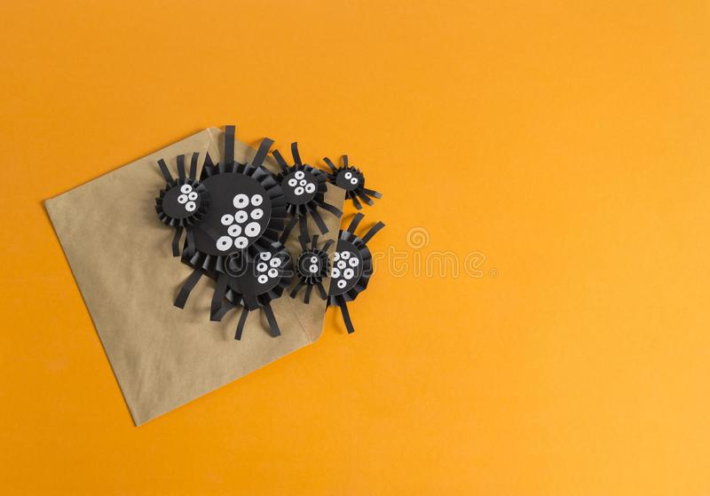 Spindlar från pappers- krypande ut ur kuvertet Orange bakgrund royaltyfri bild