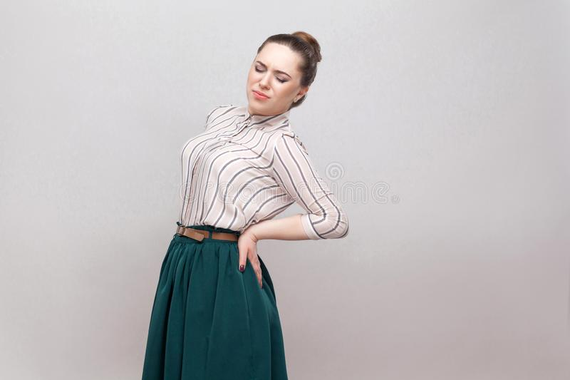 Spine or kidney pain. Portrait of beautiful young woman in striped shirt and green skirt and collected ban hairstyle, standing and royalty free stock photos