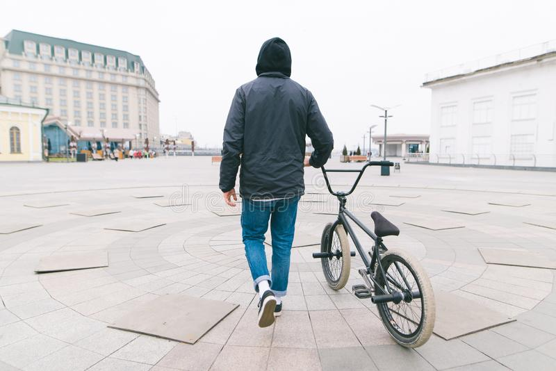young man walking around the city with a BMX bike. Walk with a bike stock photo