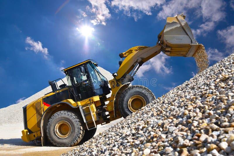 Spinga il caricatore in una cava di ghiaia durante l'estrazione mineraria - costruzione pesante fotografia stock libera da diritti