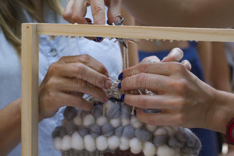 Spinnende Hände des vertikalen Webstuhls, die blaue gelbe Wolle bearbeiten lizenzfreies stockfoto