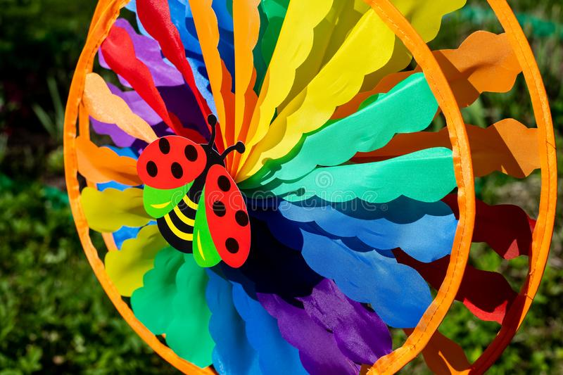 Spinner toy on green nature background.multi colored round pinwheel in motion, in sunny garden. Big round rainbow. Spinner toy , Big round rainbow pinwheel in stock images