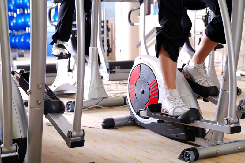 Spinning bike in a gym. Woman working out at spinning byke at fitness gym stock photo
