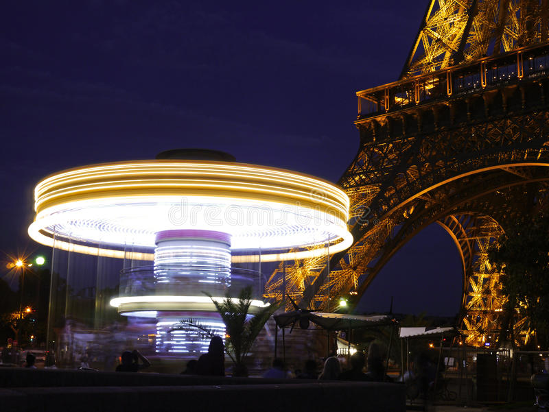 Spinning carousel under the Eiffel Tower at Night stock photo