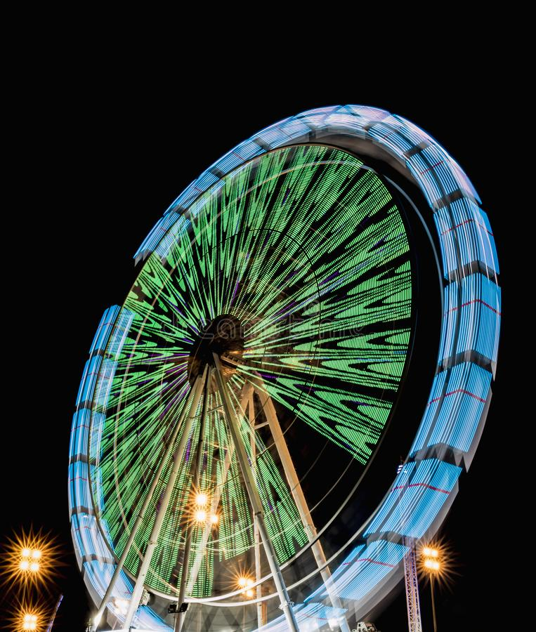 Spinning ferris wheel at night in a park of distractions with beautiful colors royalty free stock images