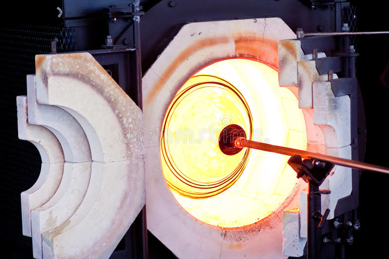 Spinning Molten Glass in Oven. A glass blower spinning molten glass on a rod in an oven stock photos
