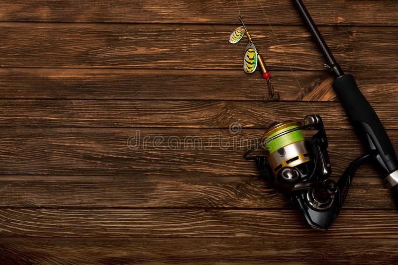 Spinning with a reel on an old brown wooden background. Metal Fishing lure. Beautiful relief boards. Carbon rod. Fishing. Summer. royalty free stock photo