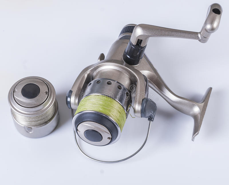 Spinning reels on a white background. Fishing accessories. Spinning reel with fishing line wrapped around the green on a white background. not royalty free stock images