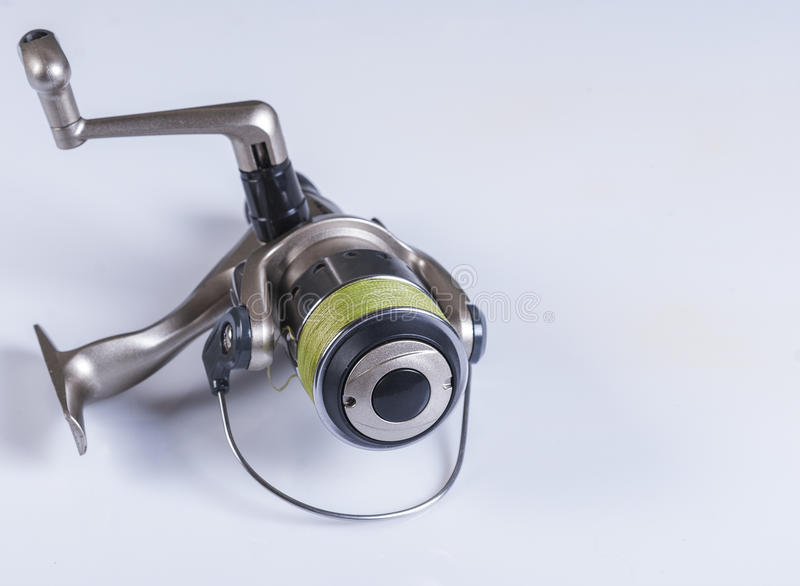 Spinning reels on a white background. Fishing accessories. Spinning reel with fishing line wrapped around the green on a white background. not isolated stock photo