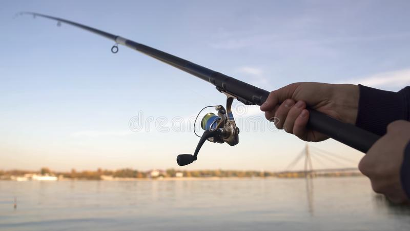 Spinning rod closeup, man fly-fishing near river, active leisure, weekend stock image
