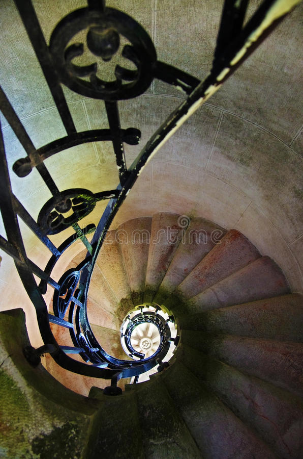 Spinning Staiway. Spiral stone staircase with metallic rails stock photos