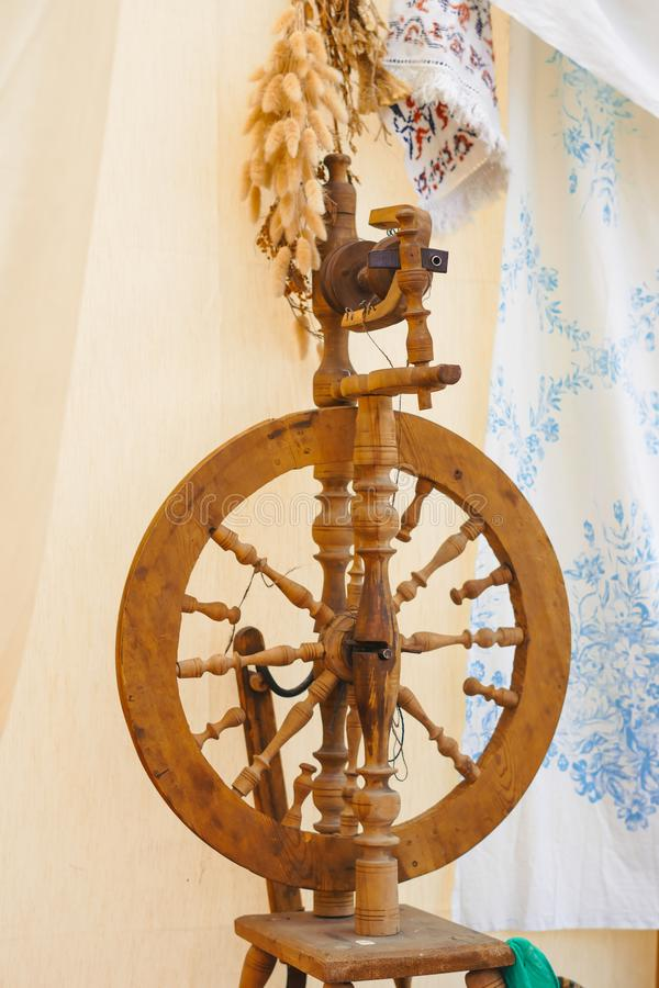 A spinning wheel with yarn baskets and old chair. On a log cabin porch royalty free stock images