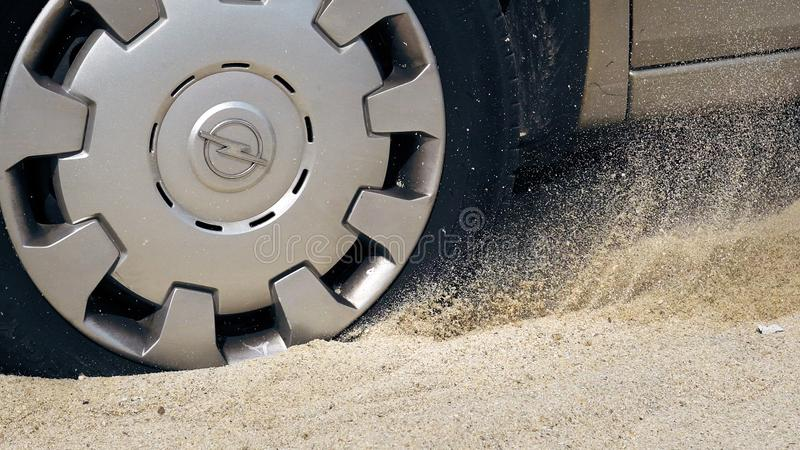 Spinnrad eines Autos gehaftet im Sand auf einem Seestrand stockfotografie