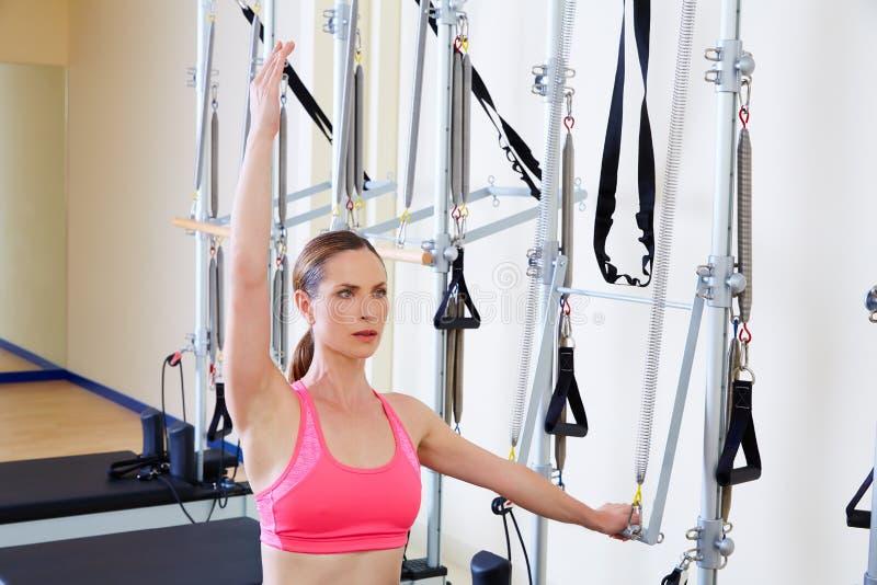 Spinta del lato della donna del riformatore di Pilates con l'esercizio immagini stock libere da diritti
