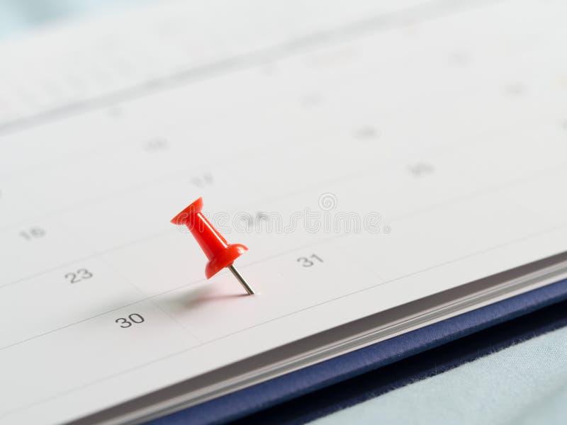 Spinta rossa del perno il giorno 31 del mese di conclusione sul calendario bianco Segni questo giorno come data di stipendio Conc immagini stock
