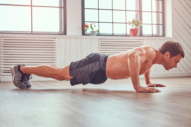 Spinta-UPS facente maschio muscolare senza camicia bello sul pavimento a casa fotografia stock