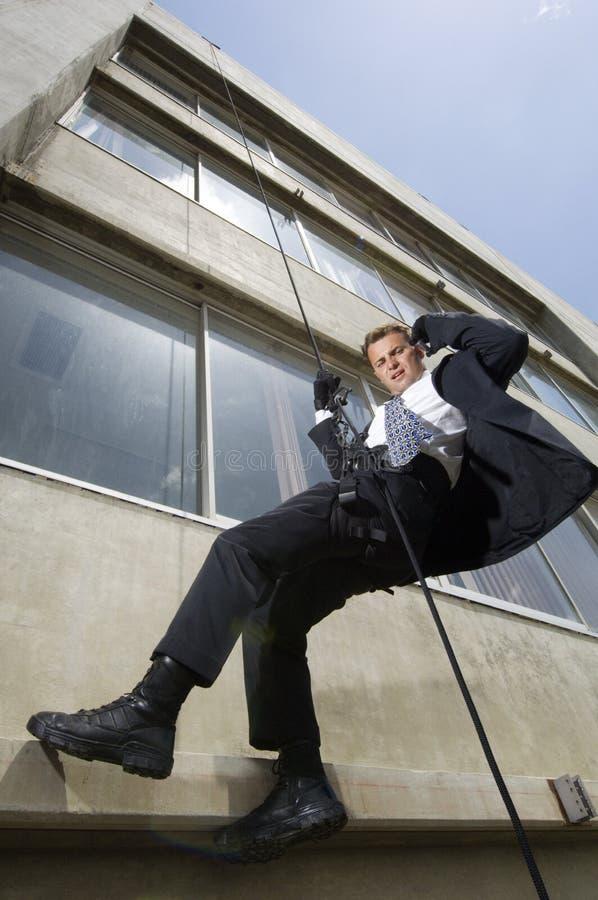 Spion som Rappelling och använder mobiltelefonen royaltyfri foto
