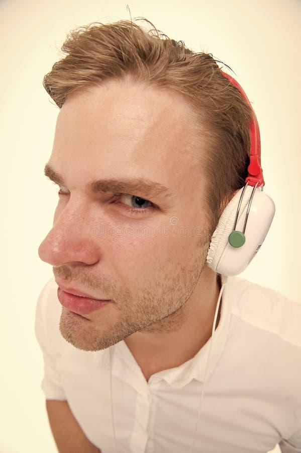 Spionbegrepp Lyssnande h?rlurar f?r man suspiciously som spion Grabben med h?rlurar lyssnar ljudet Misst?nksamt lyssna f?r man arkivfoton