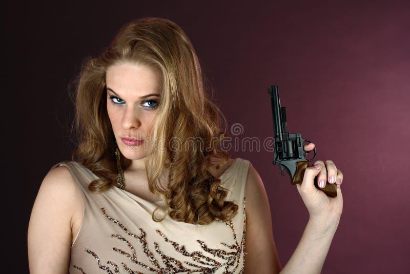 Spionieren Sie das Mädchen mit Gewehr zeigend oben auf roten Hintergrund aus stockbild
