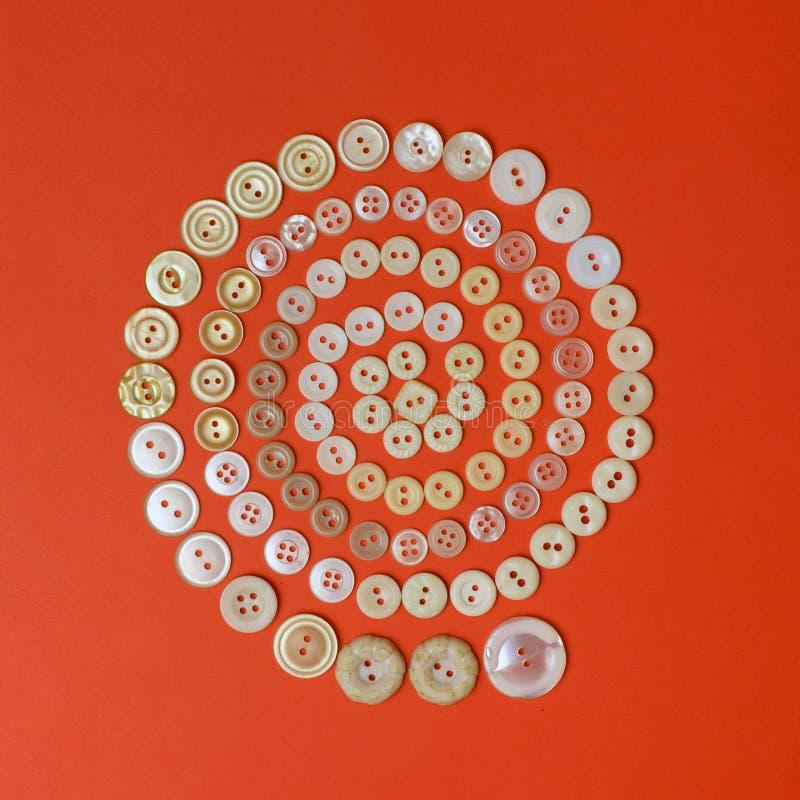 Spiraal van beige uitstekende knopen op rode achtergrond Hoogste mening stock fotografie