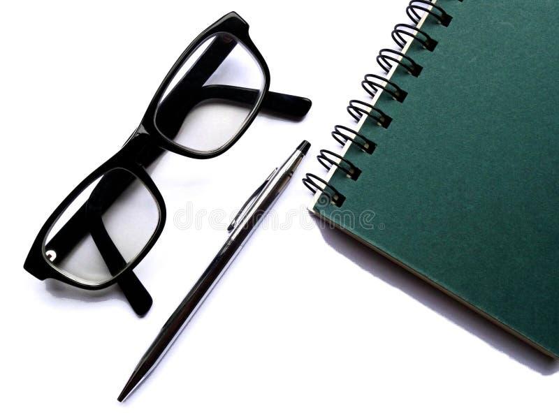 Spiraal - verbindende notitieboekje, glazen en pen op witte bedelaars stock fotografie