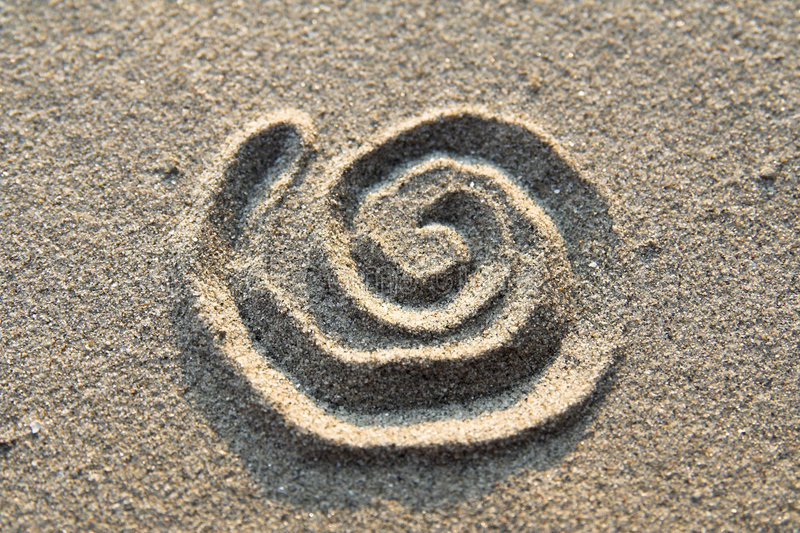 Spiralé signez dedans le sable photo libre de droits