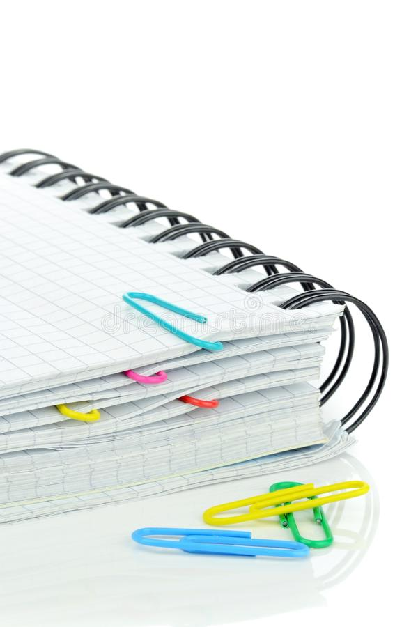 A spiral backed notebook. And coloured paperclips on white background royalty free stock photo
