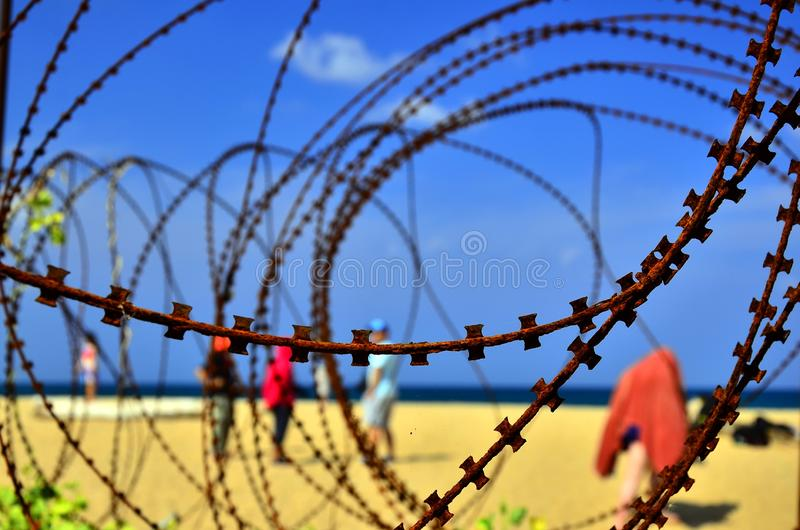 The spiral of barbed wire protects a private property from climb over a fence royalty free stock photo