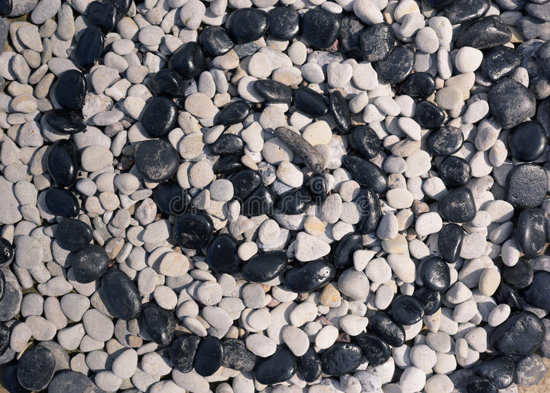 Spiral of black and white pebbles stock images