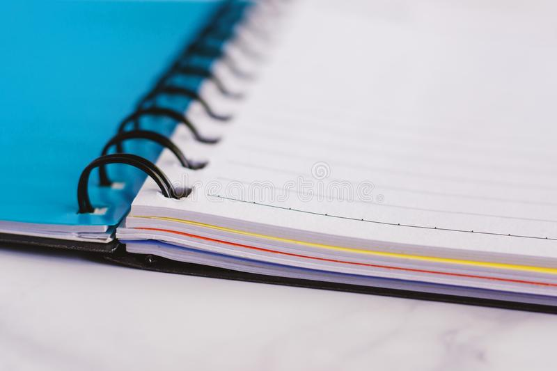 Spiral blank notebook on white marble background. For office and school supplies concept, selective focus and DOF stock photo