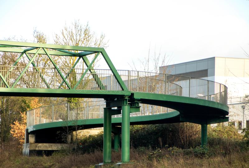 Spiral Bridge Design. A green spiral design allows pedestrians to walk up and over or over and down from the bridge crossing stock photos